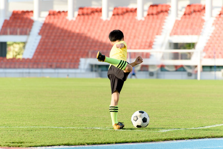 football play: Young Asian boy play on the grass football field in the stadium during summer. Stock Photo