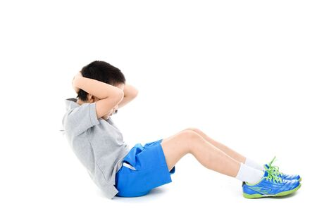 sit up: Young asian boy workout his abs muscle by sit up on white background