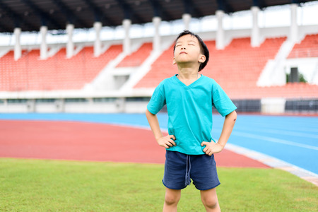during the day: Young Asian boy standing on green football field in stadium during day time and feel relax. Stock Photo