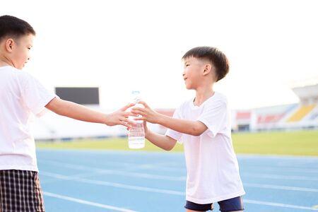 レース トラックで別の少年から水のボトルを取ってアジアの少年を実行されています。