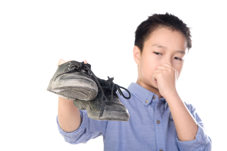 olfato: Selectivo se centran en el zapato viejo y sucio, Asia muchacho joven que se siente infeliz con mal olor zapatos de cuero negro sobre fondo blanco. Foto de archivo