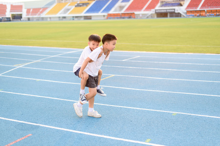 help: Boy help each other to run on the running track. Stock Photo