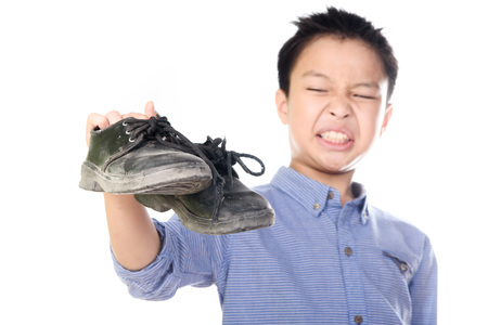 Selective focus on the old and dirty shoe, Young Asian boy feeling unhappy with bad smell black leather shoes on white background.