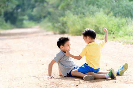 aggression: Two boy angry and figthing by punch on the other on the urban road during summer time.. Stock Photo