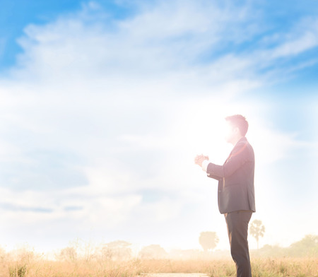 slump: Business man that face covey by strong sun light, standing and pray under blue sky white cloud.