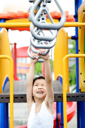 Young asian boy hang the metal bar by his hand to exercise at out door playground Stock Photo