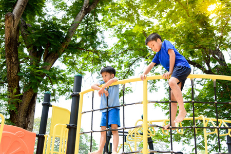 Young asian boy climb on the black rope fence and yellow bar by his hand to exercise at out door playground under the big tree.