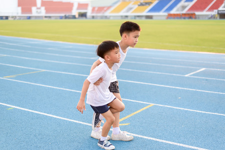 Boy help each other to run on the running track. Banque d'images