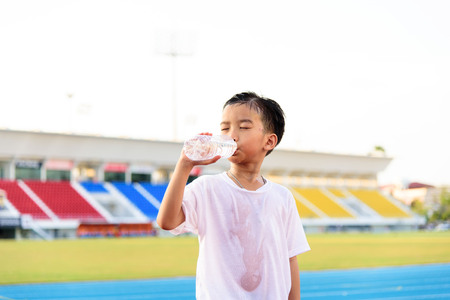 hot day: Young Asian boy drinking fresh water from plastic bottle after sport in stadium. Stock Photo