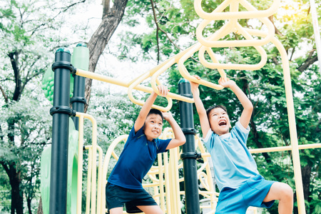 Vintage color tone, Young asian boy hang the yellow bar by his hand to exercise at out door playground under the big tree. Stock Photo