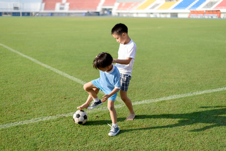 football play: Two Young Asian play football in the grass football field in the stadium during summer. Stock Photo