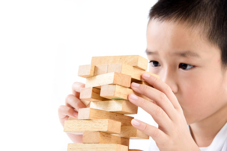 tower block: Young Asian boy try to build wooden block tower. Stock Photo