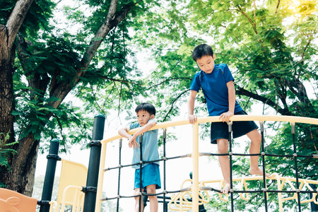 Vintage color tone, Young asian boy climb on the black rope fence and yellow bar by his hand to exercise at out door playground under the big tree. Stock Photo