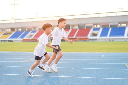 Jonge Aziatische jongen die op blauwe track in het stadion tijdens de dag de tijd om zich te oefenen.