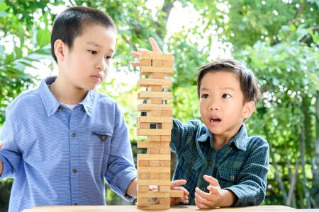 tower block: Two Young Asian boy try to build wooden block tower on green background from trees