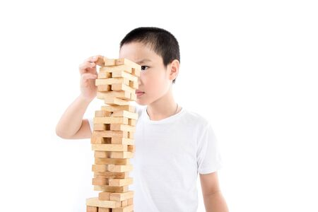 wooden block: Young Asian boy try to build wooden block tower. Stock Photo