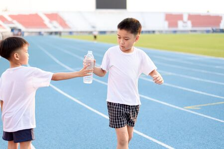 health drink: Running Asian boy taking bottle of water from another boy on the race track.