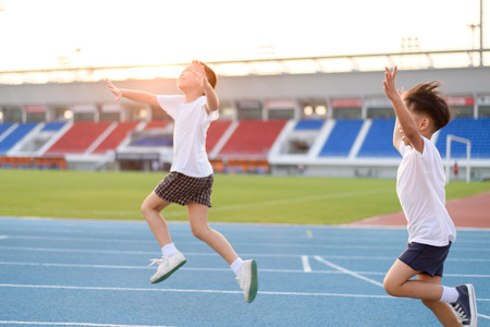 Young Asian boy running on blue track in the stadium and happy during day time to practice himself.