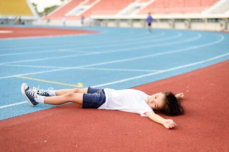 tired person: Young Asian boy tired and lay down on the running track.