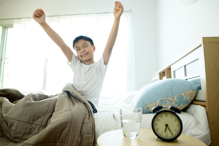 glass bed: Selective focus on the glass of water in front of the young asian boy on the bed. Stock Photo