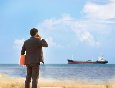slump: Business man standing on the mountain and using cell phone looking to the ship on the blue ocean. Stock Photo