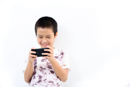 Younger Asian poor boy got a new smartphone and looks happy. Social network concept. Banco de Imagens