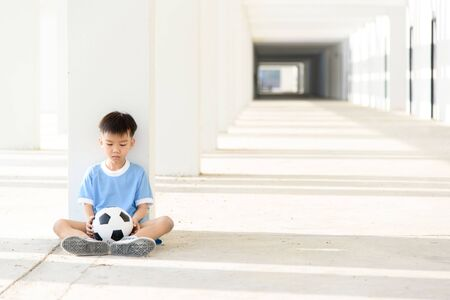 lonely boy: Lonely boy sit at the white building wth football.