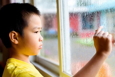 Young asian boy standing beside the window  with raindrop on the glass after raining with. Imagens