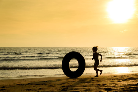 beach buoy: Silhouette young boy play a big life buoy on the beach. Stock Photo