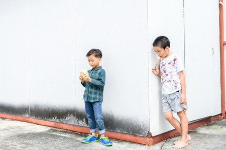 bamboo stick: Younger Asian boy eat burger but poor boy eat chickent grill from bamboo stick at the corner of old building. Poor and hungry concept.