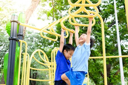 アジアの若い男の子は、大きな木の下でドア遊び場うちで運動する彼の手によって黄色のバーをハングします。