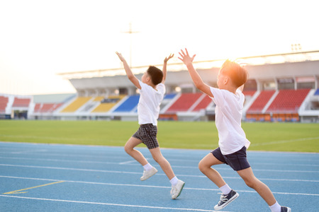 sports track: Young Asian boy running on blue track in the stadium and happy during day time to practice himself.
