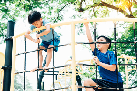 Vintage color tone, Young asian boy climb on the black rope fence and yellow bar by his hand to exercise at out door playground under the big tree. Standard-Bild
