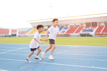 children day: Young Asian boy running on blue track in the stadium during day time to practice himself.