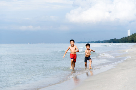 swim suit: Boy in swim suit run in on the beach and sea at Thai island.