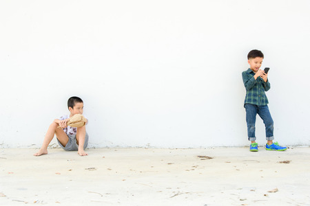 boys playing: Younger Asian boy play smartphone but another poor boy looks unhappy and lonely at the white wall. Social network concept. Stock Photo