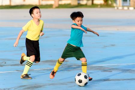 アジアの若い男の子は夏の間にフットボールを青のコンクリートの床に。 写真素材