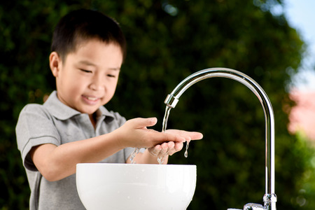 pouring water: Close up kid hand under the brand new faucet. Stock Photo