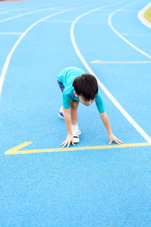 during the day: Young Asian boy prepare to start running on blue track in the stadium during day time to practice himself.