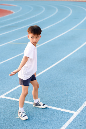 alone boy: Young Asian boy prepare to start running with another boy on blue track in the stadium during day time to practice himself.