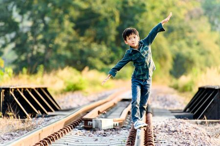 Young asian Thai boy walking on the railway at the country side of Thailand with forest background