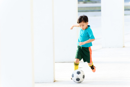 football play: Young Asian boy play football in the empty white building. Stock Photo
