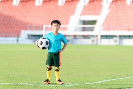 Jonge Aziatische jongen staan op het voetbalveld gras in het stadion tijdens de zomer.
