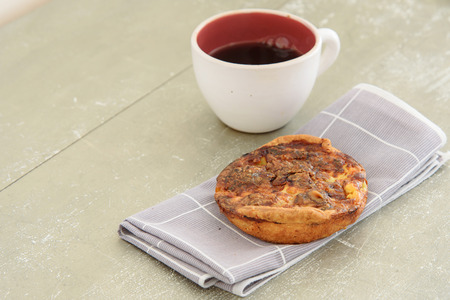 dry fruit: Selective focus. Home mad almond and dry fruit pie on old table. Out focus coffee cup Stock Photo