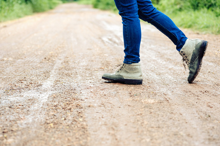 urban road: Dak color tone. Woman traveller in boot walk on the wet dirty road in urban forest.