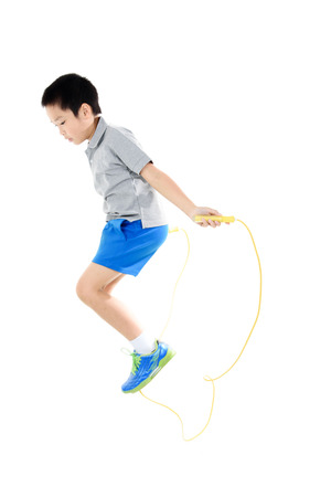 man jump: Young asian boy excercise with yellow rubber rope jumping on white background