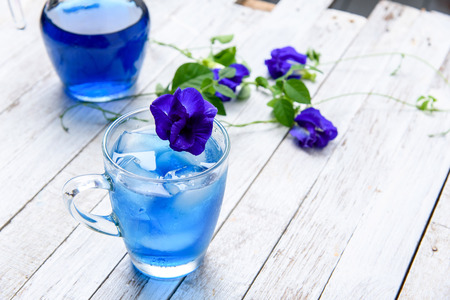 Butterfly pea juice with ice in trasparent cup serve on wooden table with flower. 版權商用圖片