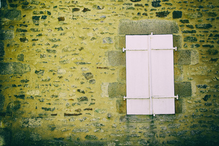 vignetted: Vintage color tone and vignetted effect. white wood window on the stone wall Stock Photo