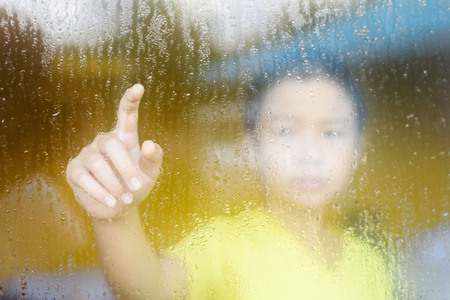 reflect: Young asian boy standing beside the window  with raindrop on the glass after raining with. Stock Photo