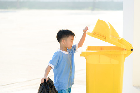 Young Asian boy carry garbage in plastic bag for eliminate in the yellow bin under the sunligh